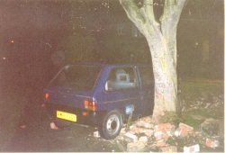 Car wedged between tree and remaining bricks....